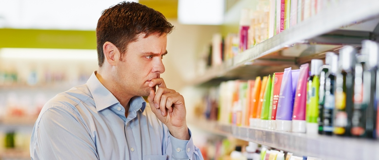 Pensive man in supermarket making a sustainable shopping decisio